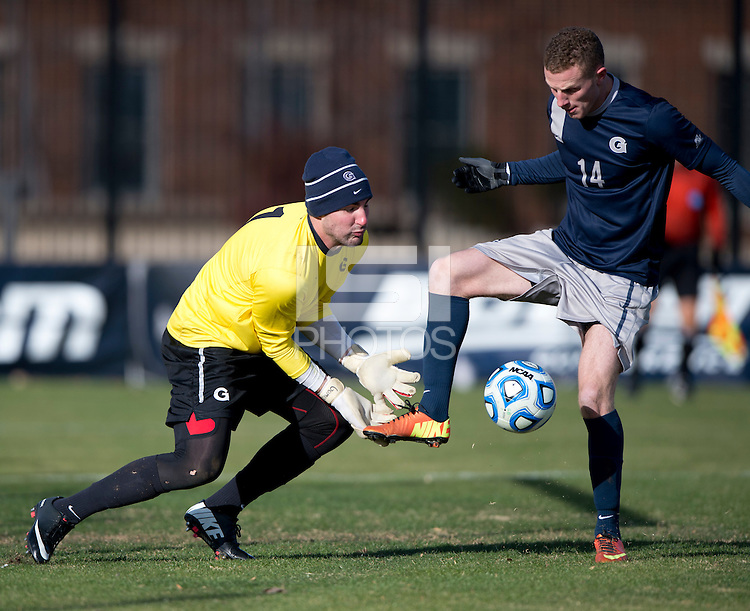 Tomas Gomez (1) of Georgetown has the ball kicked away from his hands by teammate Cole Seiler (14) during the second round of the NCAA tournament at Shaw Field in Washington, DC. Georgeotown defeated Old Dominion, 3-0.