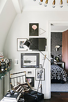 An elegant black angle poise lamp stands in one corner; behind it a collection of artworks is displayed on the wall.