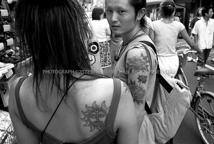 "8/10/2002--Shimokitazawa, Tokyo, Japan..Tattoos, once associated with yakuza gangsters and never shown in public, are now cool for Japanese youth...Wedged between Tokyo's Shinjuku and Shibuya wards, Shimokitazawa's maze of narrow streets form the ramparts of all that is non-conformist in get-along, go-along Japan. In ""Shimokita,"" old village shops trade happily beside newer, eccentric clothing stores, funky restaurants, matchbox playhouses and live-music clubs. The unpretentious ambience is a magnet for students and other young visitors for whom Tokyo's usual street fashion scene has become more fascist than fun and mainstream entertainment is, well, too mainstream. Musicians, designers, aspiring actors and other would-be iconoclasts have settled the area, as have young professionals opting for a less-structured lifestyle. ...All photographs ©2003 Stuart Isett.All rights reserved.This image may not be reproduced without expressed written permission from Stuart Isett."