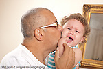 13 month old baby girl at home held by father her primary caregiver comforted crying distraught sad horizotnal