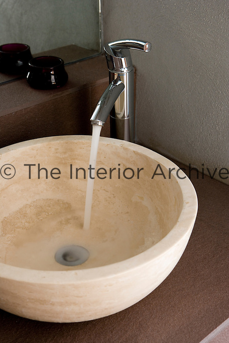 In the bathroom a round travertine wash basin has been paired with a stainless steel tap designed in a pared-down minimalist style