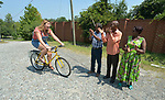 Monique Lohmeyer, a case manager for Church World Service, demonstrates for three refugees how to ride a bike in Durham, North Carolina. <br /> <br /> Church World Service, which resettles refugees in North Carolina and throughout the United States, works with the Durham Bicycle Co-op to provide bikes to newly arrived refugees.<br /> <br /> <br /> <br /> Photo by Paul Jeffrey for Church World Service.