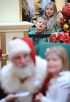 STAFF PHOTO ANDY SHUPE - Joshua Casto, 6, and his sister, Lauren Casto, 11, of Rogers watch Santa Claus while while waiting in line to have their photograph made with him Monday, Dec. 22, 2014, in the Northwest Arkansas Mall in Fayetteville.