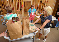 NWA Democrat-Gazette/BEN GOFF &bull; @NWABENGOFF<br /> Susan Barr pushes takes a cart of food to waiting families on Friday Aug. 14, 2015 while volunteering with the Shepherd's Food Pantry program at Bella Vista Lutheran Church. The program, which distributes bags of food to members of the community each Friday, has grown from helping feed 1346 people in 2010, it's first year, to helping 6837 in 2014, according to a press release. An expansion and remodeling project at the church is nearing completion and has doubled the space available to the food pantry program.