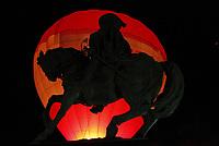 Statue of Juan Bautista de Anza on his horse, seen against the light at night with the background of a red hot air balloon in the city of Hermosillo, Sonora.<br /> ..Estata de Juan Bautista de Anza en su caballo, vista a contra luz en la noche con el fondod e un Globo aerostático de color rojo en la ciudad de Hermosillo, Sonora.