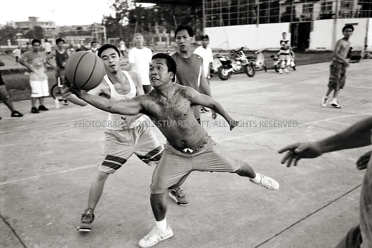 11/25/2006--Phnom Penh, Cambodia..Heng Sophea, aka 'Wicked', and other deportees play local kids at basketball most Sunday afternoons. When the deportees first starting arriving in Phnom Penh such weekend games were more common but as the years move on, the deportees have started breaking up into smaller, more scattered groups across Phnom Penh...Photograph By Stuart Isett.All photographs ©2006 Stuart Isett.All rights reserved.