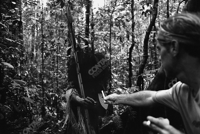 Tour guide Kelly Woolford offers a kreteks (local clove cigarettes) to tribesmen. West Papua, Indonesia, September 2004.