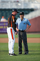 Aberdeen IronBirds manager Kevin Bradshaw (25) discusses a call with first base umpire Roberto Pattison during the game against the Hudson Valley Renegades at Leidos Field at Ripken Stadium on July 27, 2017 in Aberdeen, Maryland.  The Renegades defeated the IronBirds 2-0 in game one of a double-header.  (Brian Westerholt/Four Seam Images)
