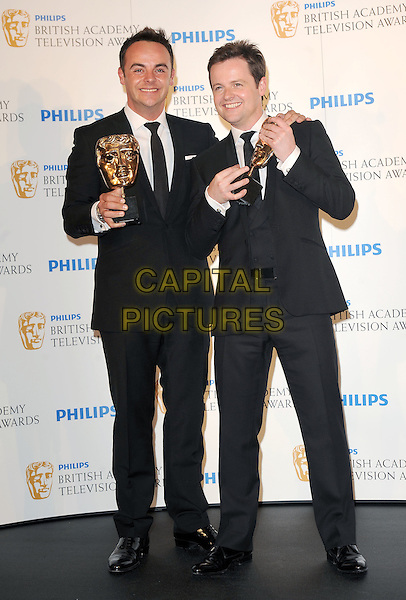 ANT & DEC - Anthony McPartlin & Declan Donnelly.in the press room at the Philips British Academy Television Awards (BAFTA) at the London Palladium in London, England, June 6th, 2010..BAFTAs TV  full length winners trophy black suit tie white shirt .CAP/BEL.©Tom Belcher/Capital Pictures.