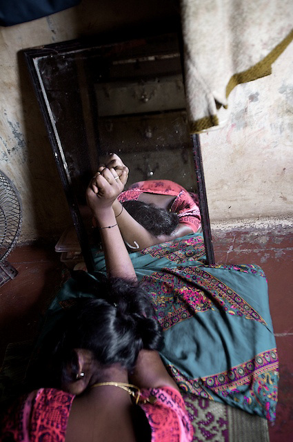 "Saraswati, 16, sleeps in the brothel where she lives and works. She tries to sleep as much as possible between clients so that she ""does not have to think""."