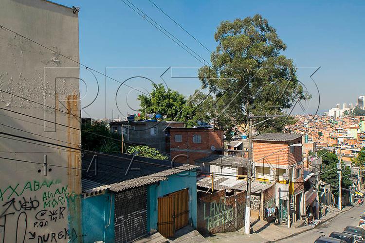 Rua na Favela Paraisópolis e edifícios ao fundo, São Paulo - SP, 06/2016.
