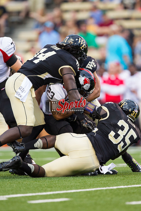 Juanne Blount (23) of the Gardner Web Runnin' Bulldogs is tackled by Zachary Allen (35) and Wendell Dunn (14) of the Wake Forest Demon Deacons during first half action at BB&T Field on September 6, 2014 in Winston-Salem, North Carolina.  The Demon Deacons defeated the Runnin' Bulldogs 23-7.   (Brian Westerholt/Sports On Film)