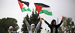 Palestinian protesters wave their national flags in front of Israeli security forces during a protest marking the Palestinian Land Day in the West Bank village of Nabi Saleh near Ramallah, March 28, 2015. Land Day commemorates the unrest that erupted in March 1976 when Israeli Arabs protested the Israeli government's confiscation of thousands of acres of Arab-owned land and in which six Arab citizens were killed by Israeli police. Photo by Shadi Hatem