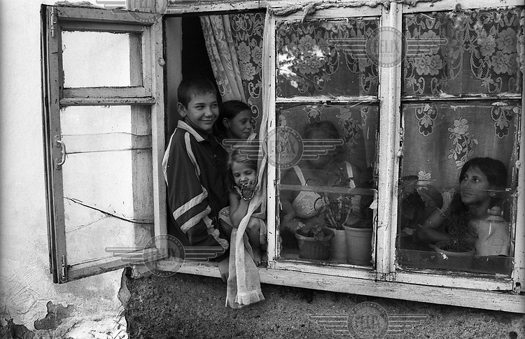Children sit on the window sill of their house at an open window while their mother looks out from inside.