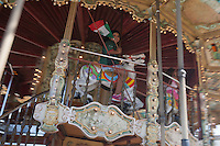 Los Angeles, CA -  Monday, June 23, 2014: A young Mexico fan  celebrates Mexico's victory over Croatia in a first round match riding a carousel at Plaza Mexico.