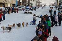 Marcelle Fressineau runs into the finish chute to claim 49th and last place at Nome on Saturday March 15 during the 2014 Iditarod Sled Dog Race.<br /> <br /> PHOTO (c) BY JEFF SCHULTZ/IditarodPhotos.com -- REPRODUCTION PROHIBITED WITHOUT PERMISSION