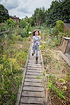 © Joel Goodman - 07973 332324 . 27 July 2013 . Hulme Community Garden Centre , Old Birley Street , Hulme , Manchester M15 , UK . Mum Kerrie Wilson's daughter AMY WILSON (eight) (correct) (from Rusholme) runs along the roof garden . Hulme is Where the Art Is festival . Photo credit : Joel Goodman