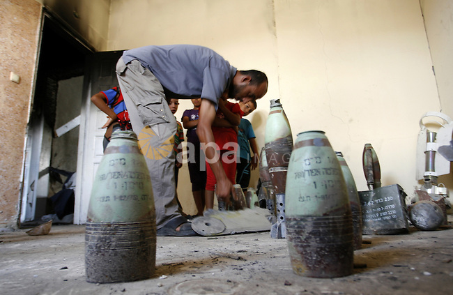 """Palestinian resident, Suleiman Abu Jamaa, 35, displays mortars and other types of ammunition that he collected around his destroyed home in Khan Yunis in the southern Gaza Strip on September 11, 2014. Israel's deputy foreign minister,Tzahi Hanegbi , warned that Hamas was likely to resume """"violence"""" if it feels it has made no political gains from upcoming talks in Cairo. Photo by Abed Rahim Khatib"""