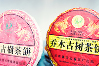 Puehr Tea Cakes in brightly coloured red and yellow paper wrappers, for sale in a tea shop in Hong Kong.