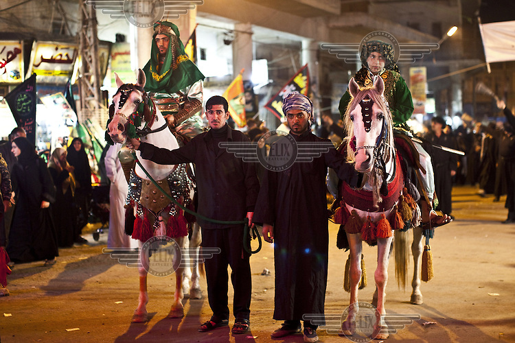 A pair of ornately dressed horses and riders, meant to represent Hussein's horse Zuljina, on Ashura during Muharram. Ashura marks the anniversary of the Battle of Kerbala and is a period of intense grief among Shi'ite followers of Islam. ..