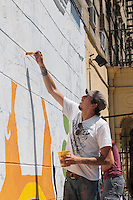 The artist Raul Ayala works with volunteers on Brook Avenue in the Melrose neighborhood of the Bronx in New York on Saturday, August 9, 2014 to paint a mural about police violence and community safety. Designed Ayala the painting project was organized by the Justice Committee, Caav: Organizing Asian Communities and Streetwise & Safe.  (© Richard B. Levine)