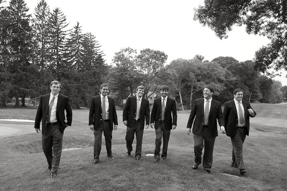 Black & white shot of the groom with his groomsmen walking on the golf course.