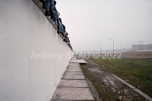 Berlin, East Germany<br /> November 12, 1989<br /> <br /> Germans sit on top of the Berlin Wall at Potsdamer Platz to look at sections of the wall that were removed. Germans gathered as the wall is dismantled and the East German government lifted travel and emigration restrictions to the West on November 9, 1989.
