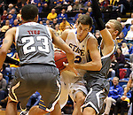 BROOKINGS, SD - JANUARY 18:  Brayden Carlson #12 from South Dakota State University takes the ball to the basket against the defense of Marcus Tyus #23 and Caleb Steffensmeier #12 from Omaha in the first half of their Summit League game Saturday afternoon at Frost Arena in Brookings. (Photo by Dave Eggen/Inertia)