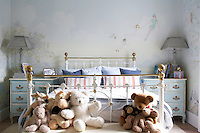 A child's pretty bedroom with a fairy mural painted on the walls. A brass and painted iron bed has two blue painted chests of drawers either side.