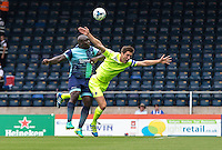 A slight nudge from Adebayo Akinfenwa of Wycombe Wanderers on Luke Prosser of Colchester United during the Sky Bet League 2 match between Wycombe Wanderers and Colchester United at Adams Park, High Wycombe, England on 27 August 2016. Photo by Liam McAvoy.