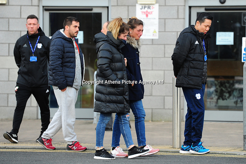 Pictured: Sala's sister Romina Sala (centre) and Cardiff City CEO Ken Choo (right) pays tribute for Emiliano Sala laid down outside the Cardiff City Stadium in south Wales, UK. Friday 25 January 2019<br /> Re: Premier League footballer Emiliano Sala was on a flight which disappeared between France and Cardiff.<br /> The Argentine striker was one of two people on board the Piper Malibu, which disappeared off Alderney on Monday night.<br /> Cardiff City FC, signed the 28-year-old from French club Nantes.