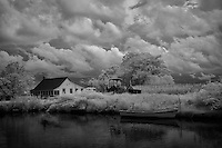 Black/white infrared image of landscape with farmhouse, tractor and boat
