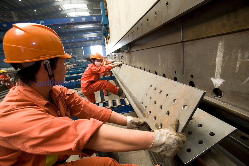 Workers with steel plates from a bending machine in a factory, Changxing Island, Shanghai, China