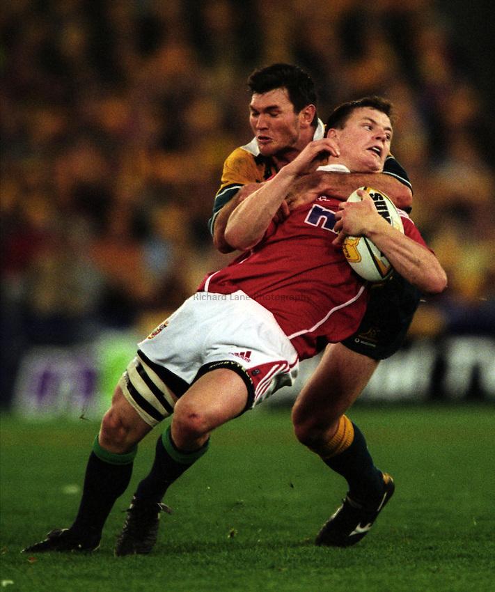 Photo. Richard Lane. .Australia v Bristish and Irish Lions. Lions Tour 2001 to Australia. Third Test at the Stadium Australia, Sydney, Australia. 14/7/2001..Brian O'Driscoll is tackled high by Daniel Herbert.