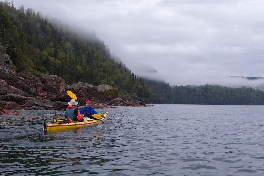 Sea kayakers paddle a tandem kayak on a foggy morning in Lake Superior Provincial Park near Wawa Ontario Canada.