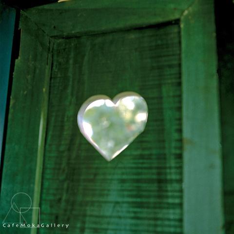 Heart in green wooden window shutter