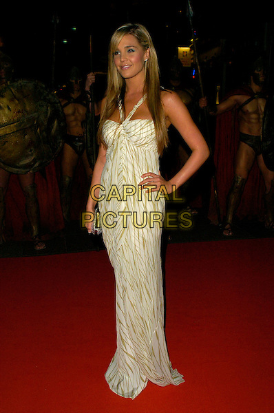 "DANIELLE LLOYD.UK Premiere of ""300"" at Vue West End, Leicester Square, London, UK..full length white beige green pattern dress halterneck silver clutch purse hand on hip .CAP/CAN.©Can Nguyen/Capital Pictures"