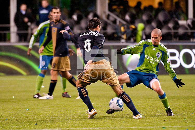 Osvaldo Alonso (r) goes for the ball against Stefani Miglioranzi (6) as the Seattle Sounders defeated the Philadelphia Union, 2-0, in an MLS match on Thursday, March 25, 2010 at Qwest Field in Seattle, WA. It was the Sounders home opener and the first regular season game for the expansion Philadelphia Union.
