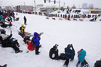 Saturday, March 3, 2012  Spectators watch Peter Kaiser round the turn at 4th and Cordova during the Ceremonial Start of Iditarod 2012 in Anchorage, Alaska.