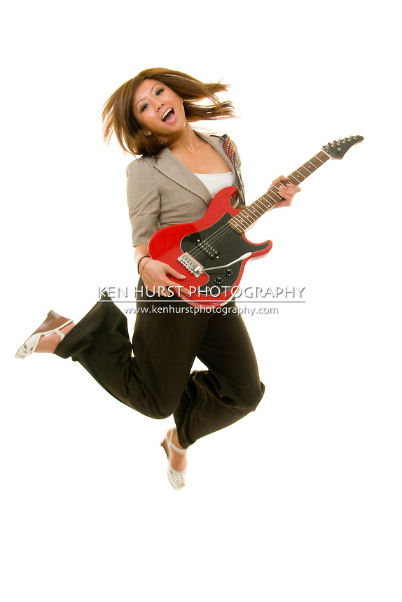 Young Asian adult woman jumping up in the air while playing guitar.  Shot on white. Substantial motion blur from moving, jumping subject.