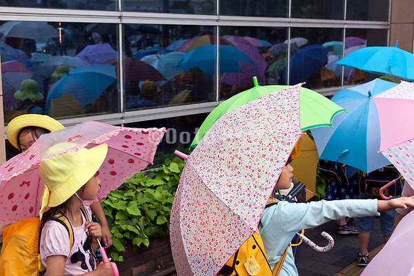 group of little school children walking with bright colored umbrellas Kyoto Japan