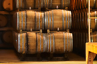 Rows of oak barrels stacked four high with fermenting wine. Giraud is specialised in oak aging champagne. Champagne house Maison Giraud-Hemart, also called Champagne Henri Giraud, Ay, Vallée de la Marne, Champagne, Marne, Ardennes, France, low light grainy grain