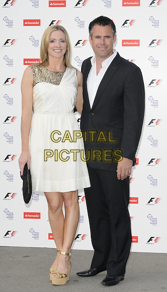 GABBY LOGAN & KENNY LOGAN.The F1 Party held at the Natural History Museum, London, England, UK..5th July 2010.Formula one full length white cream gold grecian dress beaded embellished studded platform ankle strap shoes wedges black suit husband wife married clutch bag.CAP/CAN.©Can Nguyen/Capital Pictures.
