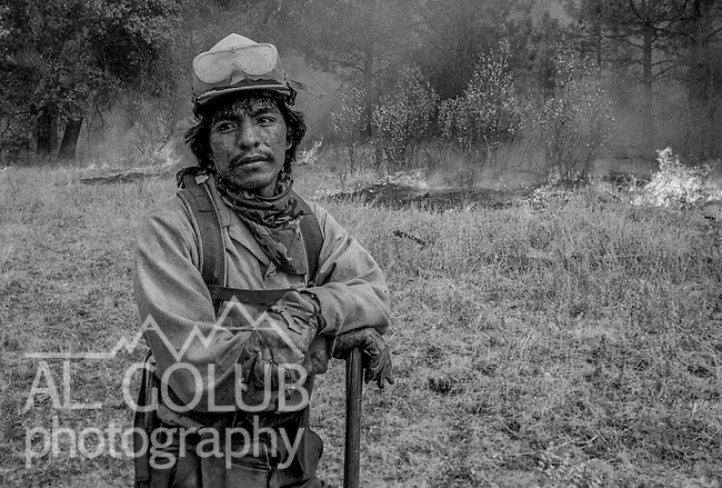 September 1, 1987 Buck Meadows, California -- Stanislaus Complex Fire -- Truxton Canyon Firefighter from Bureau of Indian Affairs looks for spot fires to protect fire camp. The Stanislaus Complex Fire consumed 28 structures and 145,980 acres.  One US Forest Service firefighter, David Ross Erickson, died from a tree-felling accident.