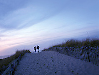Two people walking at dusk on sandy path to beach. Cape Cod National Seashore, Massachusetts.