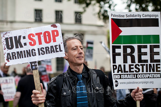 Peter Tatchell (Social justice campaigner). <br /> <br /> London, 23/08/2014. Hundreds of people gathered outside 10 Downing Street to call the British Government to stop all the arms related trade with Israel (&lt;&lt;which were worth &pound;180m in the period 2008-2012 [&hellip;] These equipment include F16 fighter jet components, assault rifles, armoured vehicles and ammunition [&hellip;]&gt;&gt;, from the Friends of Al-Aqsa - FOA - online press release). The demonstration was organised by, amongst others, War On Want, Stop The War Coalition, London Palestine Action, FOA - Friends of Al Aqsa, PSC - Palestine Solidarity Campaign, BMI - British Muslim Initiative, Palestinian Forum in Britain, and Campaign for Nuclear Disarmament.