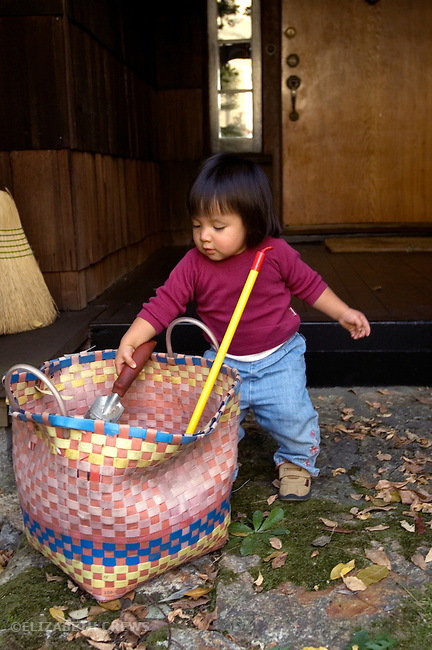 Berkeley CA Guatemalan girl, eighteen-months-old, cleaning up gardening tools  MR