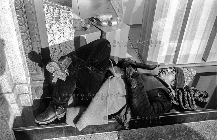 Milano, piazza Missori, zona centro. Senzatetto, barbone, dorme davanti a un negozio con dei pacchi regalo in vetrina --- Milan, Missori square, downtown. A homeless sleeping in front of a shop with gift packages displayed in the window