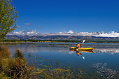 A kayaker paddles along the foreshore of the irrigation reservoir  Lake Opuha near Fairlie with the Sherwood range in the distance,Mackenzie District, Canterbury, South Island, New Zealand.