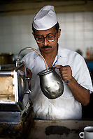 A barista warms milk for coffee from an ancient espresso machine in the Indian coffee house, Baba Kharak Singh Marg. The coffee house dates back almost fifty years, first in central Connaught Place, then Janpath and now at the top of a rather shabby shopping centre. Where it is still run by the Indian Coffee Workers Cooperative Society. Once a regular haunt for politicos in Delhi, its clientele is still renowned for being well-read and intellectual.